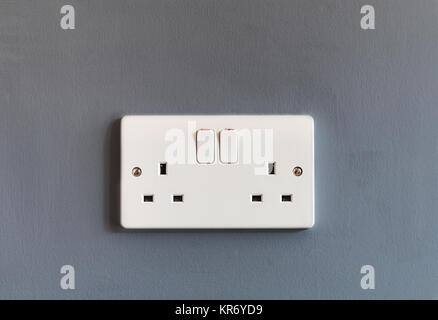 UK domestic 3 pin double plug electrical socket in white plastic on a grey coloured wall - Stock Photo