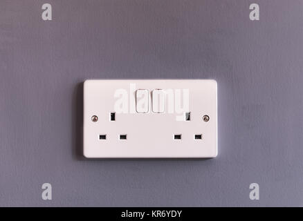 UK domestic 3 pin double plug electrical socket in white plastic on a plum coloured wall - Stock Photo