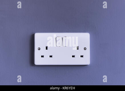 UK domestic 3 pin double plug electrical socket in white plastic on a purple coloured wall - Stock Photo