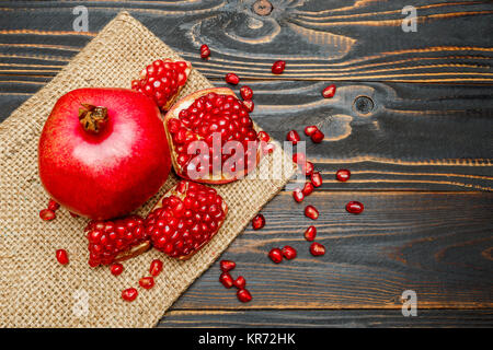 Pomegranate and seeds close-up on wooden background - Stock Photo