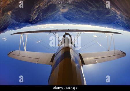 1928 Sterman Biplane flying over Aspen, CO USA - Stock Photo