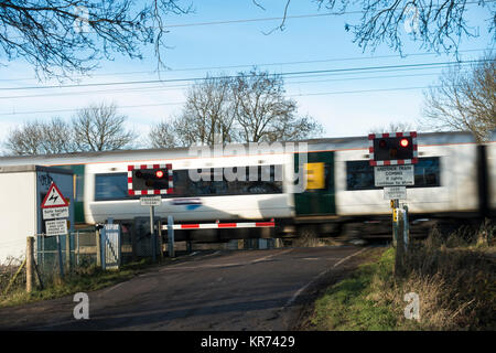 Passenger train passing over level crossing - Stock Photo