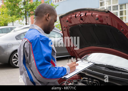 Mechanic With Clipboard In Front Of A Car - Stock Photo