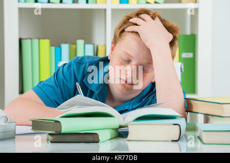 Exhausted Boy Studying In Library - Stock Photo