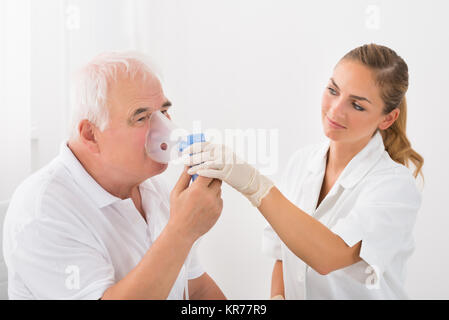 Patient Inhaling Through Oxygen Mask - Stock Photo