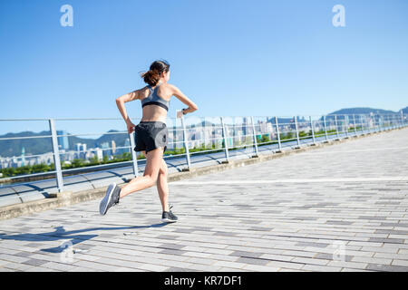 Woman using smart watch and running in a city - Stock Photo
