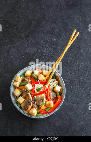 Stir fry with udon noodles, tofu, mushrooms and vegetables. Asian vegan vegetarian food, meal, stir fry over black - Stock Photo
