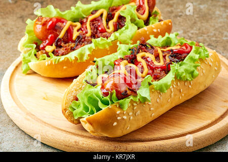 Two homemade hot dogs with lettuce, bacon and onion toppings  - Stock Photo