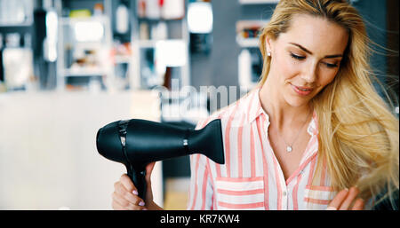 Smiling young woman blow drying hair - Stock Photo