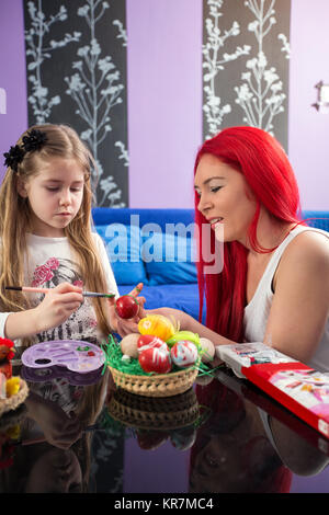 happy family painting Easter eggs -Mother and young daughter - Stock Photo