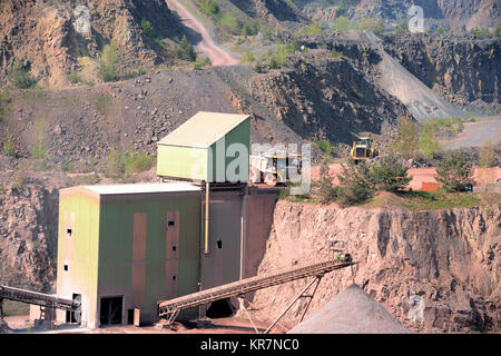 Stonecrusher machine in an active quarry mine of porphyry rocks. digging. - Stock Photo