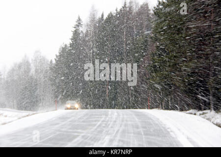 Car driving along a rural road during a blizzard. - Stock Photo