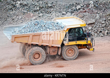 dumper truck driving in an active quarry mine of porphyry rocks. digging - Stock Photo