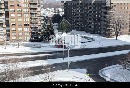 Modern condo buildings with huge windows and balconies and the snow removal tractor in Montreal, Canada. - Stock Photo