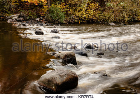 A small rapids, with upper pool reflections, on the Manitowish River near Boulder Junction, Wisconsin in early October - Stock Photo