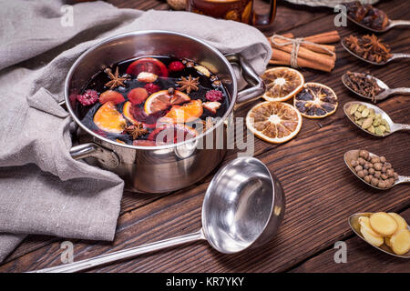 mulled wine in a pot with handles and ingredients for making a home made alcoholic drink on a brown wooden background, - Stock Photo