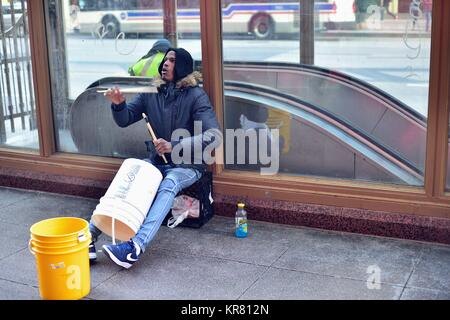A street musician between a CTA subway entrance and Macy's department store on State Street in Chicago, Illinois, - Stock Photo