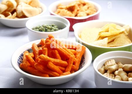 Photo of assorted chips and junk food in bowls - Stock Photo