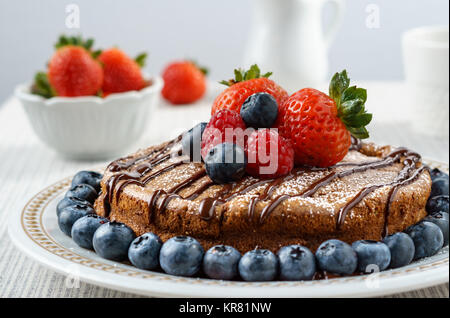 Big chocolate cheesecake with blueberry strawberry raspberry on a round plate. - Stock Photo