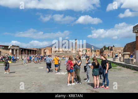 Tourists in the ruins of the Roman Forum at Pompeii ( Pompei ) looking towards Mount Vesuvius in the background, - Stock Photo