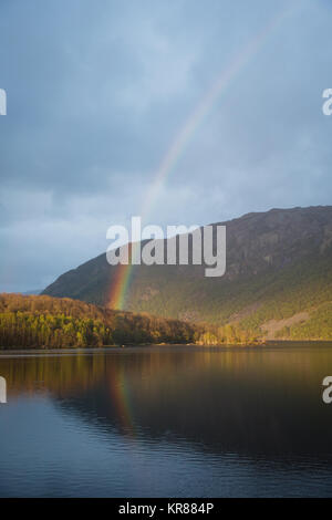 A rainbow over a lake and rolling hills in Norway - Stock Photo