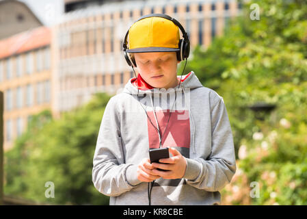 Boy Wearing Yellow Cap Listening To Music