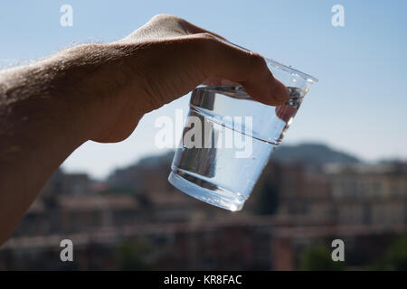 a slanted glass of water in a hand with urban defocused background. - Stock Photo
