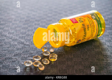 An open bottle of Vitamin D (D3) supplement pills/ tablets against grey background - Stock Photo