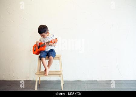 Asian Little boy playing ukulele - Stock Photo
