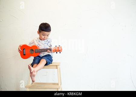 Asian boy playing ukulele - Stock Photo
