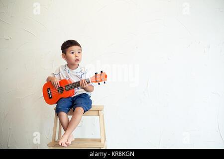 Asian boy playing guitar - Stock Photo