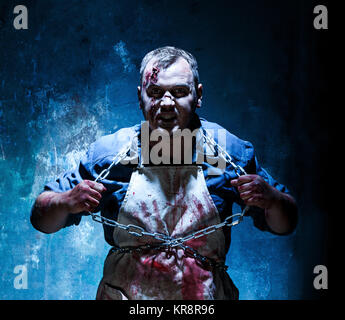 Bloody Halloween theme: crazy killer as butcher - Stock Photo