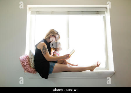 USA, Utah, Salt Lake City Mother sitting with daughter (12-17 months) on windowsill and reading book - Stock Photo