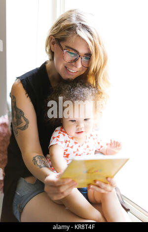 Mother sitting with daughter (12-17 months) on windowsill and reading book - Stock Photo