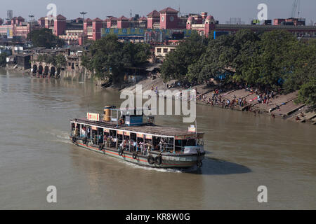 Passenger steam ferry on the Hooghly River with Howrah Railway Station in the background, Kolkata, India - Stock Photo
