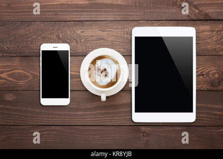 white phone tablet and coffee cup on wood table top view - Stock Photo