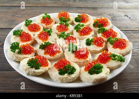 Canapees covered with butter, red caviar and parsley - Stock Photo