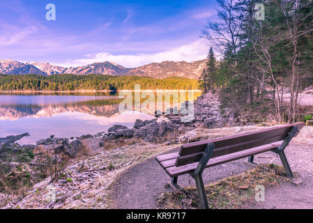 Bench on the shore of an alpine lake - Stock Photo