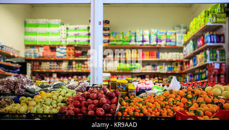 Fruits and olives in row with details. Blurred products in market store. Close up view. - Stock Photo