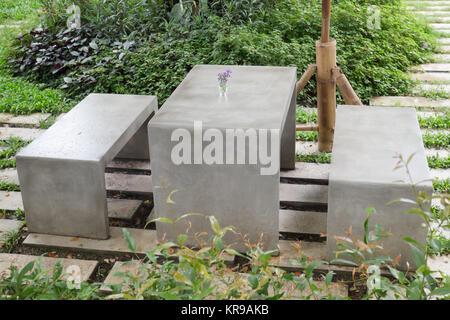 Concrete outdoor furniture set in the small garden - Stock Photo