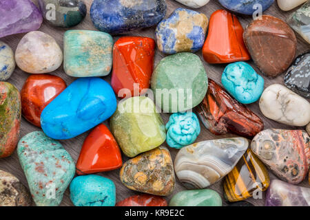 background of colorful, polished, semiprecious stone on grained wood - Stock Photo