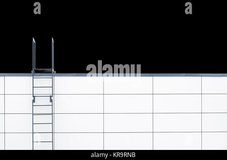 Metal emergency stairs on white wall - Stock Photo
