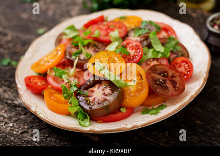 Summer salad of tomatoes of different colors with green herbs and pepper. - Stock Photo