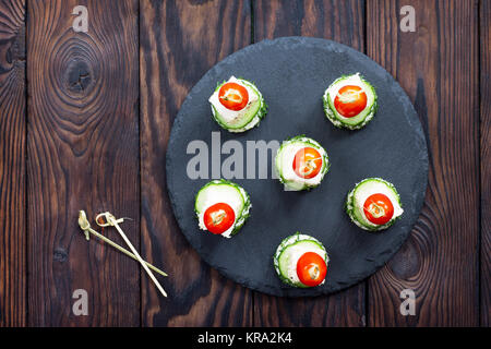 Appetizer canape with white bread, feta cheese, cucumber and cherry tomatoes on a wooden table. - Stock Photo