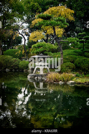 Japanese Zen garden with a lantern and a pond in Osaka Castle Park, beautiful tranquil autumn scenery. Osaka, Japan - Stock Photo