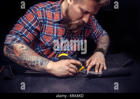 Currier producing a leatherwork at his workshelf./Craftsman works with leather goods in his tanner shop. - Stock Photo