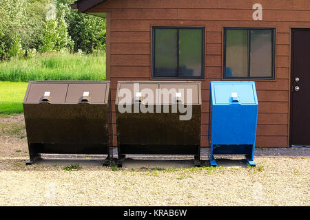 Four bear proof garbage cans with a recycle bin. - Stock Photo
