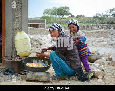 Leh, India - Jul 21, 2015. A Tibetan woman with her son at a village in Nubra Valley, India. 65% of children attend - Stock Photo
