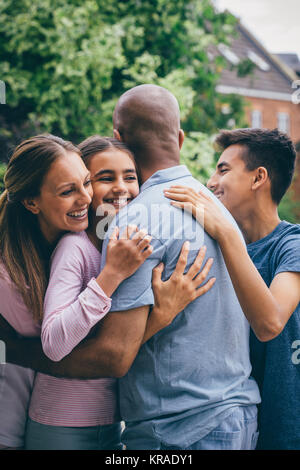 Family Cuddle Outdoors - Stock Photo