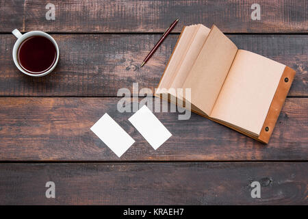 Office desk table with cup, notebook, cards on wooden table - Stock Photo